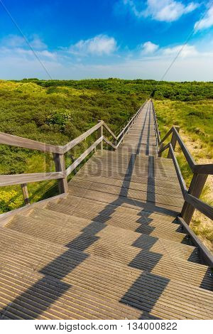 Wooden Staircase Going Into Blue Sky Among Dunes And High Grass, De Haan, Belgium