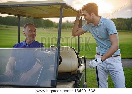 Golfing buddies. Smiling mature golfer seating in golf cart with her partner standing alongside