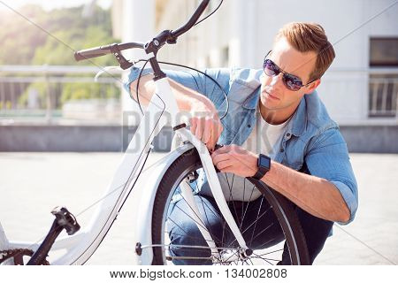 Little crash. Handsome concentrated young guy repairing a wheel on his bike before riding