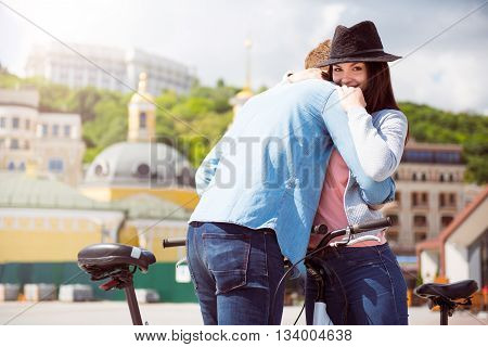 So good. Contended young woman hugging a man while standing with bicycles and looking at the camera