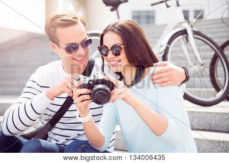 I like it. Contended beautiful young woman in sunglasses showing photos on the camera to a smiling young man while sitting on the stairs