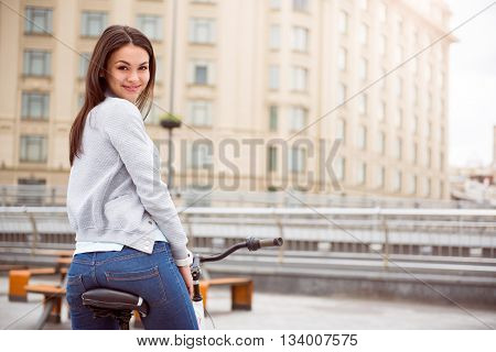 Go riding. Delighted pretty young woman looking back at camera while sitting on the bicycle
