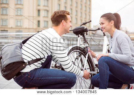Arising feelings. A young couple near the bike looking at each other with growing interest poster