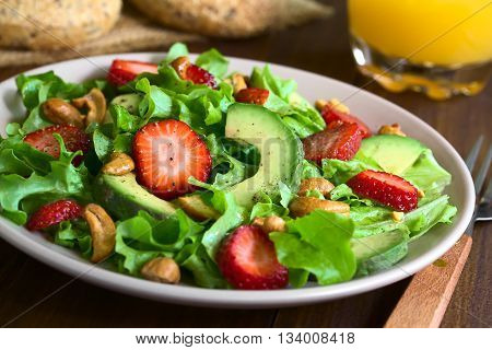 Strawberry avocado lettuce salad with cashew nuts on plate photographed on dark wood with natural light (Selective Focus Focus one third into the salad)