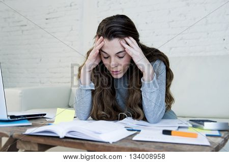 young attractive and desperate woman suffering stress doing domestic accounting paperwork bills and invoices worried and stressed at home sofa couch with laptop laptop and bank folders