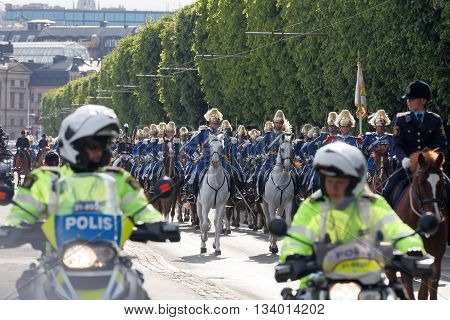 STOCKHOLM - JUN 06 2016: The Royal guards on the horse back and the motorcycle police protecting the swedish royal family on their way to celebrate the swedish national day