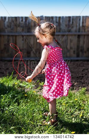 Little girl with a skipping-rope jumping in the garden.