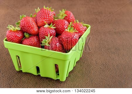 Strawberries with stems in a green container
