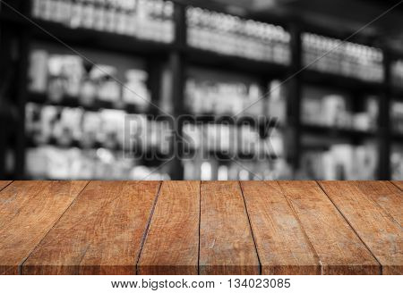 Wooden tabletop with black and white cafe blurred background, stock photo