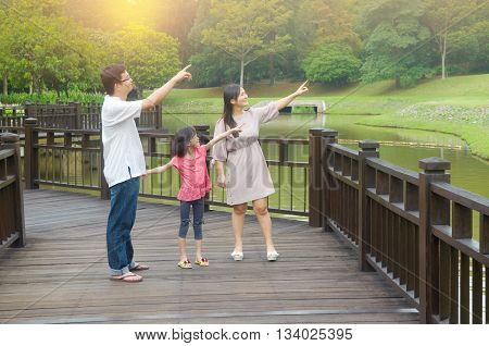 Happy Asian family pointing away outdoor lifestyle at nature green park.