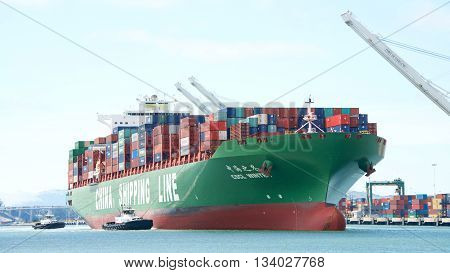 Oakland CA - June 09 2016: Multiple tugboats assisting Cargo Ship CSCL WINTER to maneuver into the Port of Oakland.