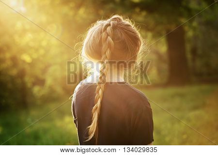 pretty teen girl standing and thining about something in park, from the back