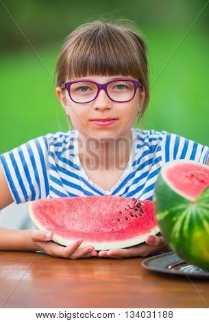 Child eating watermelon. Kids eat fruits in the garden. Pre teen girl in the garden holding a slice of water melon. happy girl kid eating watermelon. Girl kid with gasses and teeth braces.