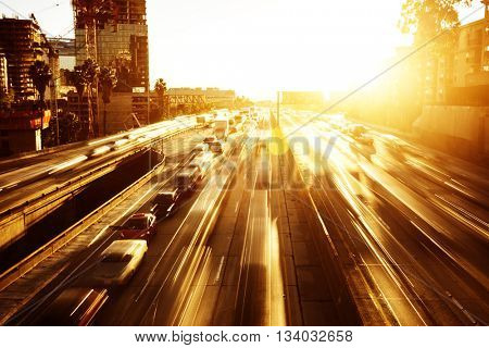 busy traffic on road in downtown of los angeles with sunbeam
