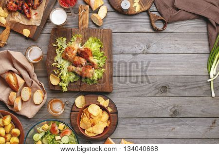 Outdoors Food Concept. On the wooden table different food with copy space grilled chicken legs buffalo wings chips bread salad potatoes and beer