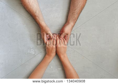 loving couple holding hands sitting at a light table top view