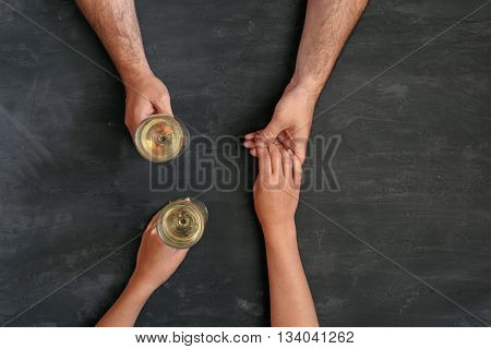 loving couple holding hands and drinking wine top view