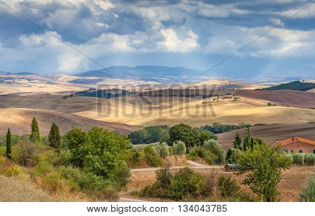 Rural landscape of Tuscany Italy. The fields hills and forests the sun's rays make their way through the clouds. Agriculture