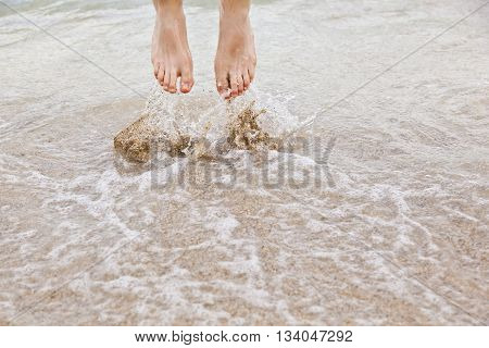 Feet Of Boy Jumping Into The Water