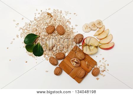 There are Banana,Apple with Walnuts and Rolled Oats,Wooden Trivet,with Green Leaves,Healthy Fresh Organic Food on the White Background,Top View.