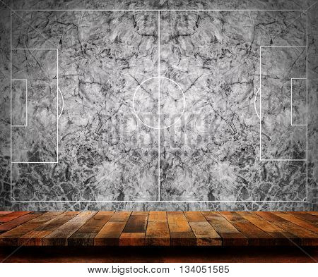 Empty wooden table with football field (bare concrete) wall background. For display or montage your products.