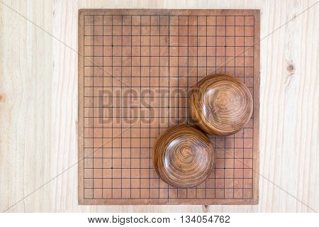 top view two wooden bowls filled black and white stones over empty go game board included clipping path traditional chinese strategy board game sport hobby and recreation