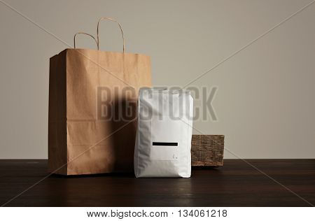 Retailer merchandise pack: big hermetic pouch white with blank label presented near of craft paper bag and rustic wooden brick on red table isolated on gray.