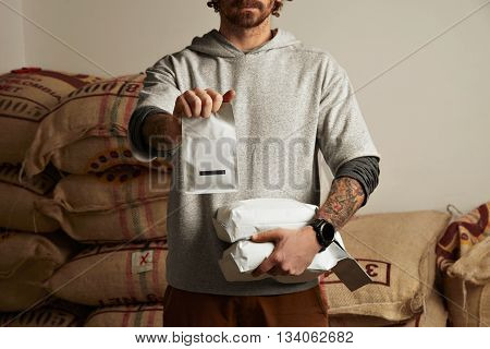 Tattooed Barista Holds Blank Package Bags With Freshly Baked Coffee Beans Ready For Sale And Deliver