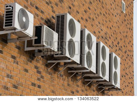 A row of air conditioners placed on the brick wall without windows