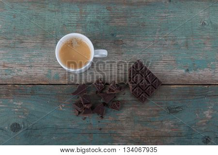 Dark chocolate and a cup of coffee on old vintage table stock photo