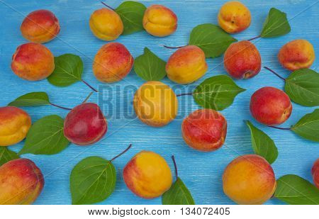 Pile of ripe red apricots on the wooden table; rural vintage concept. Concept of organic farming; fresh natural unprocessed fruit. Tilted perspective.