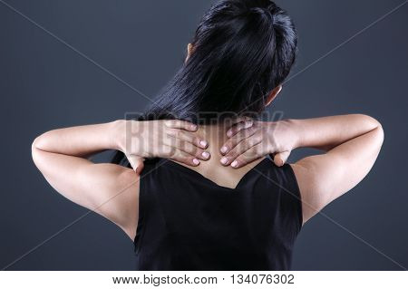 Body pain. Studio shot of beautiful young woman with dark brown hair. Woman suffering from neck ache