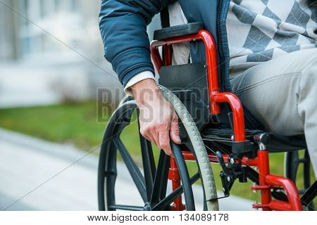 Adult man in wheelchair. Close up photo of male hand on wheel of wheelchair during walk