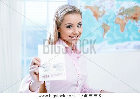 Concept for travel agent. Young blonde woman smiling, looking at camera and showing passport with visa. Travel agency office interior with big world map and window