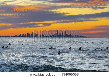 Colourful sunset over Surfers Pardise Gold Coast with surfer silhouettes in the ocean closeup