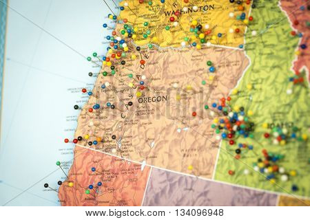 Colorful detail map macro close up with push pins marking locations throughout the United States of America OR Oregon