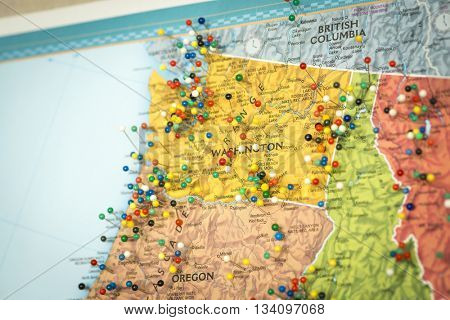 Colorful detail map macro close up with push pins marking locations throughout the United States of America WA Washington Seattle