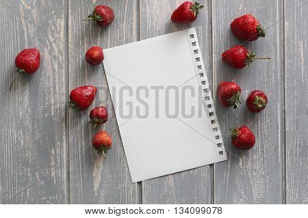 Strawberries on wooden grey desk with white paper sheet. Stock photo.