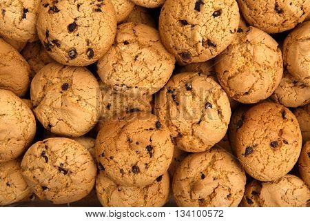 Cookies background. Sweet chocolate chips biscuits and cookies texture background. Oatmeal, chocolated drops and other sweets. Dessert, sweets for tea. Fattening sweets concept