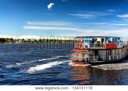 Vintage Double-deck boat with a paddle wheel on the Daugava River in Riga on a sunny day with clouds