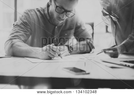 Partners meeting modern loft. Picture young creative crew working with new startup project. Work process on wood table. Idea presentation, analyze marketing plans. Blurred background, black white