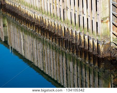 Wooden dock breakwall in a marina harbour with reflection in calm blue ocean sea