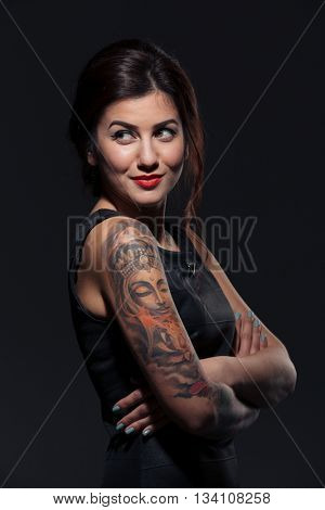 Closeup of happy tattooed young woman standing with arms crossed