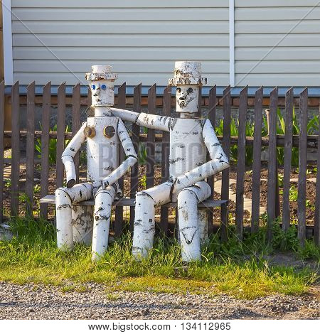 Kargat Novosibirsk oblast Siberia Russia - June 12 1916: wood sculpture of a man and woman sitting on a bench outside the house made of birch wood