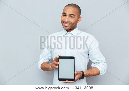 Smiling attractive african american young man holding blank screen tablet