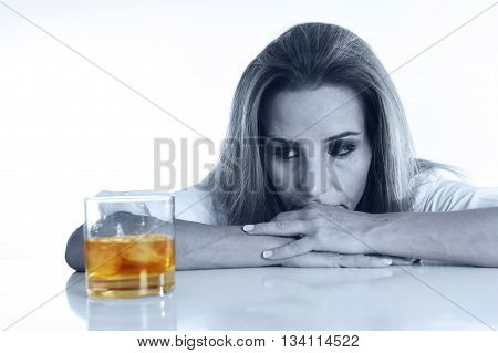 caucasian blond wasted and depressed alcoholic woman drinking scotch whiskey glass looking desperate isolated on white in alcohol abuse and addiction and housewife alcoholism problem