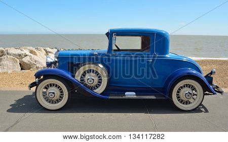 Felixstowe, Suffolk, England - May 01, 2016: Vintage  Blue Motorcar with white wall tyres parked on seafront promenade.