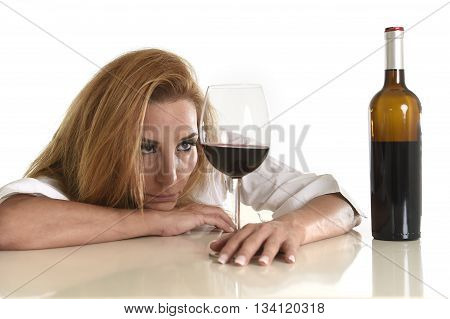 caucasian blond wasted and depressed alcoholic woman drinking red wine glass looking desperate and sad isolated on white in alcohol abuse and addiction and housewife alcoholism problem