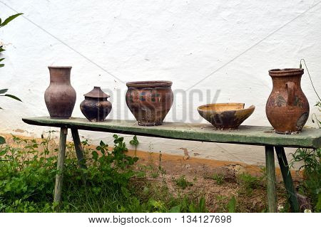 old pottery standing on a wooden bench near the white wall of the rural house