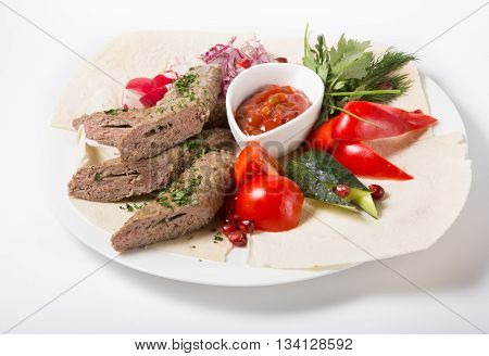 Grilled kebab meat served with onion and vegetables